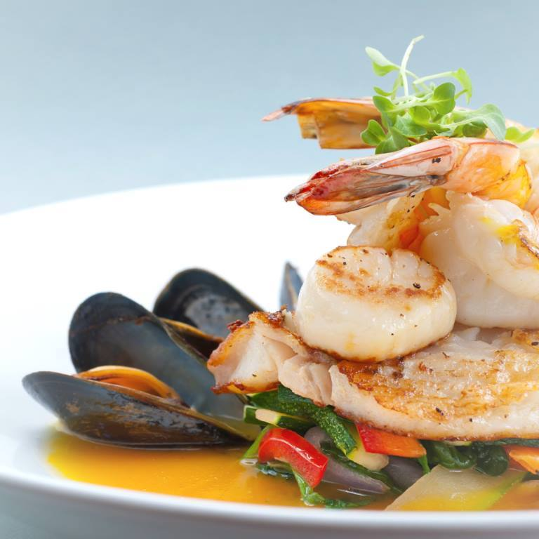 """""""Seafood medley of shrimp, scallops, mussels and fresh fish over a bed of vegetables."""""""