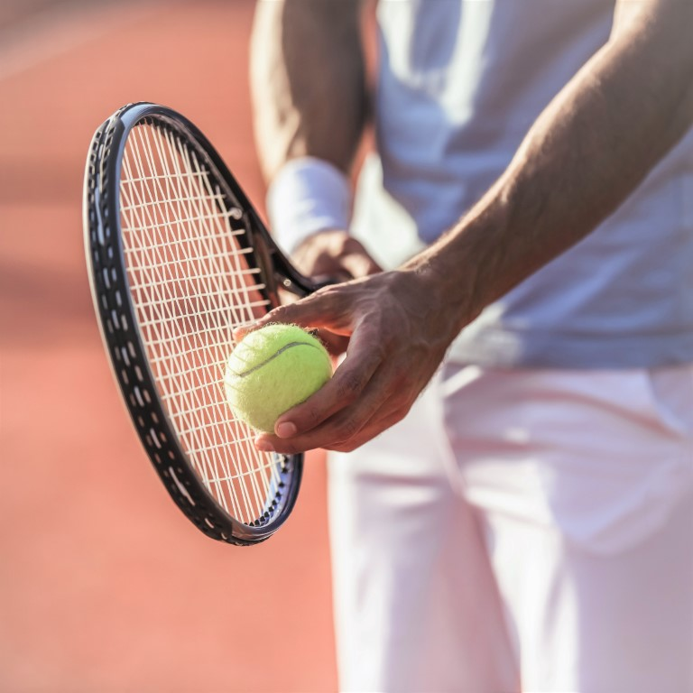 Cropped image of handsome man playing tennis on tennis court outdoors